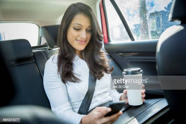 Mixed race businesswoman using cell phone in taxi