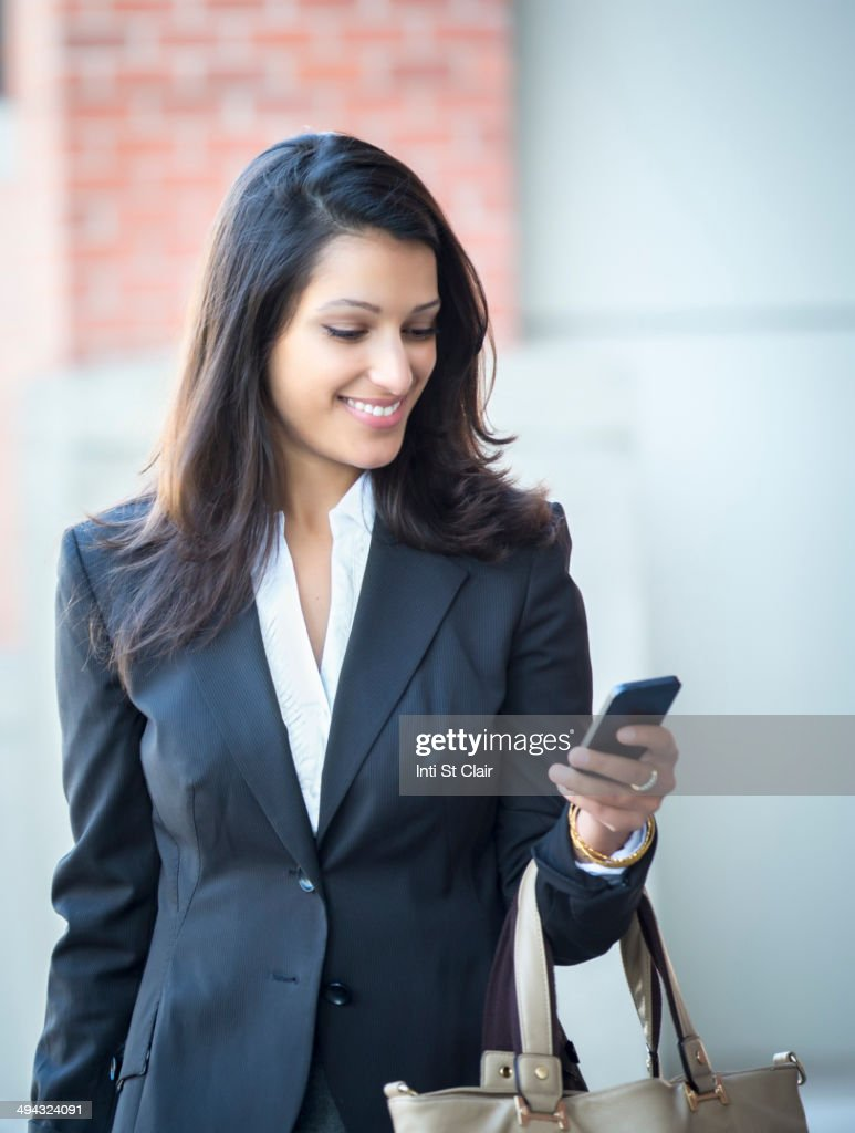 Mixed race businesswoman using cell phone on city street : Stock Photo