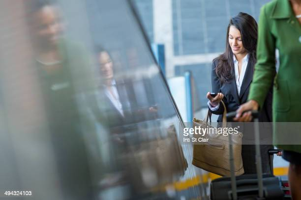 Mixed race businesswoman using cell phone on escalator