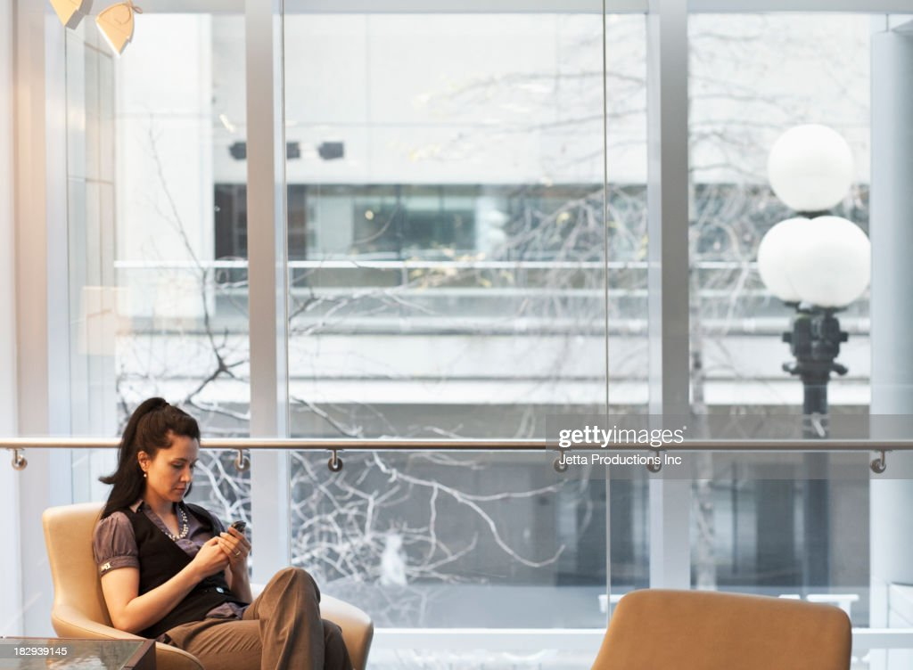 Mixed race businesswoman using cell phone