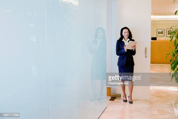 Mixed race businesswoman using digital tablet in office corridor