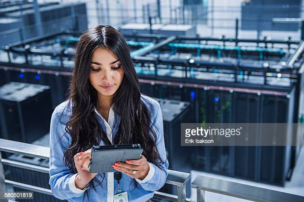 Mixed race businesswoman using digital tablet on balcony over server room