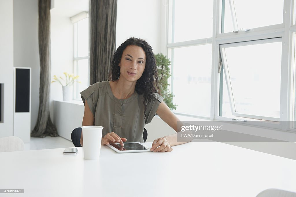 Mixed race businesswoman using digital tablet : Stock Photo