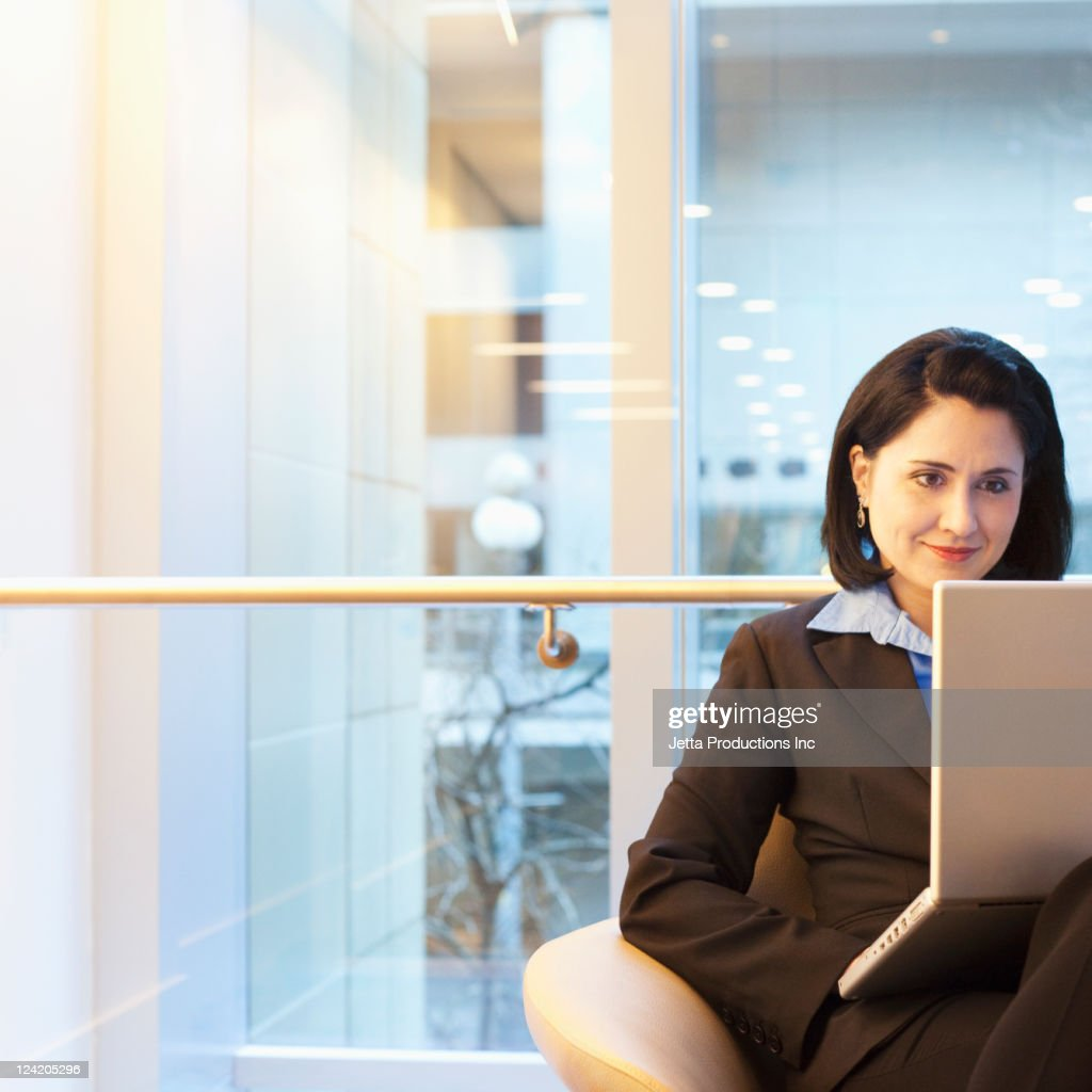 Mixed race businesswoman using laptop in office
