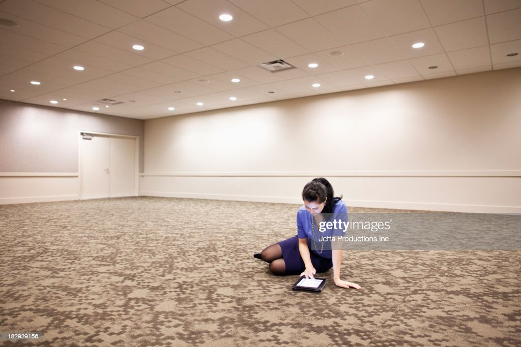 Mixed race businesswoman using tablet computer in empty room