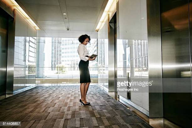 Mixed race businesswoman using tablet computer in lobby