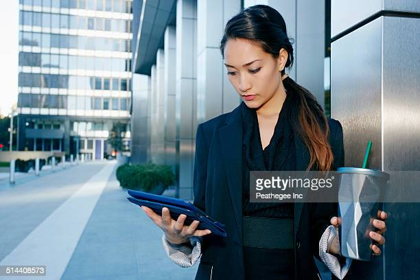 Mixed race businesswoman using tablet computer on city street