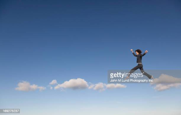 Mixed race businesswoman walking on clouds