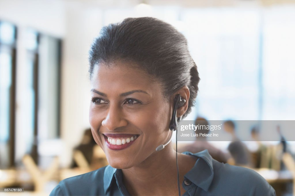 Mixed race businesswoman wearing headset in office