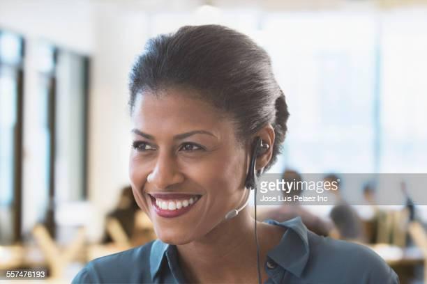 Mixed race businesswoman wearing headset in office