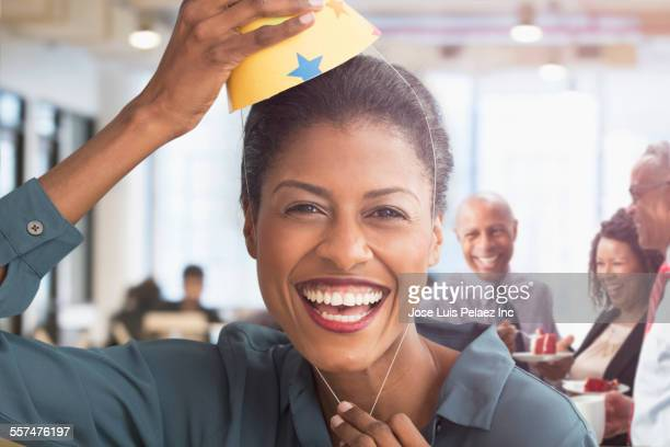 Mixed race businesswoman wearing party hat in office