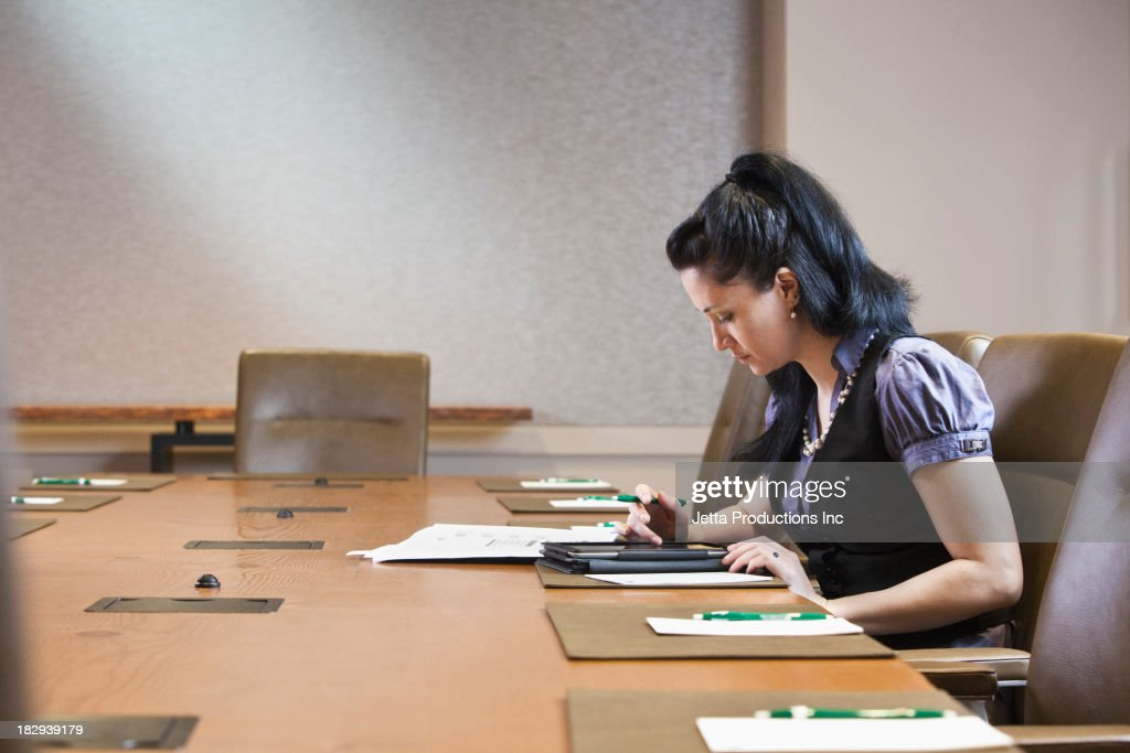 Mixed race businesswoman working at meeting table