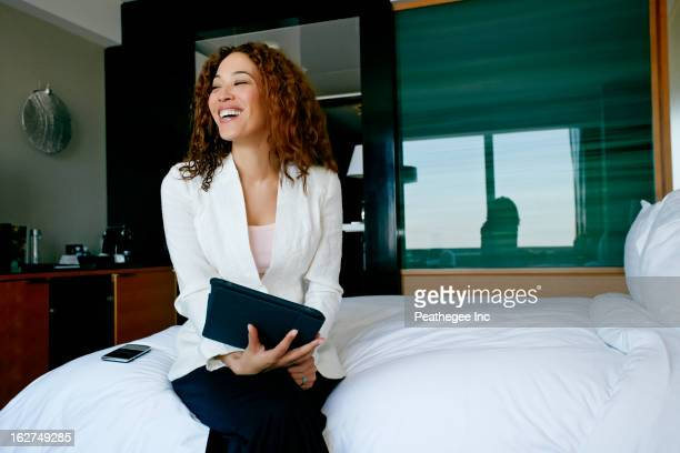 Mixed race businesswoman working in hotel room