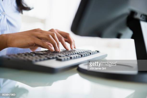 Mixed race businesswoman working on computer