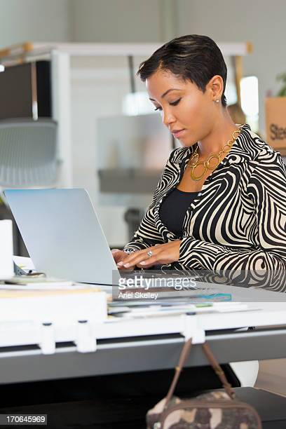 Mixed race businesswoman working on laptop