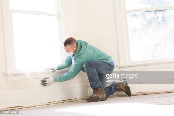 Mixed race carpenter cleaning wall