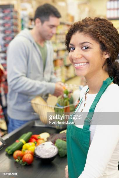 Mixed Race cashier at grocery store