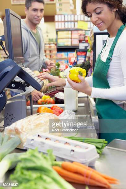 Mixed Race cashier ringing up groceries