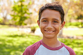 Mixed race Caucasian Asian boy in park looking to camera
