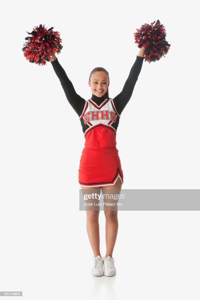 Mixed race cheerleader holding pom-poms