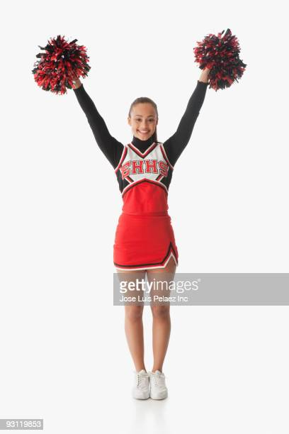Mixed race cheerleader holding pom-poms