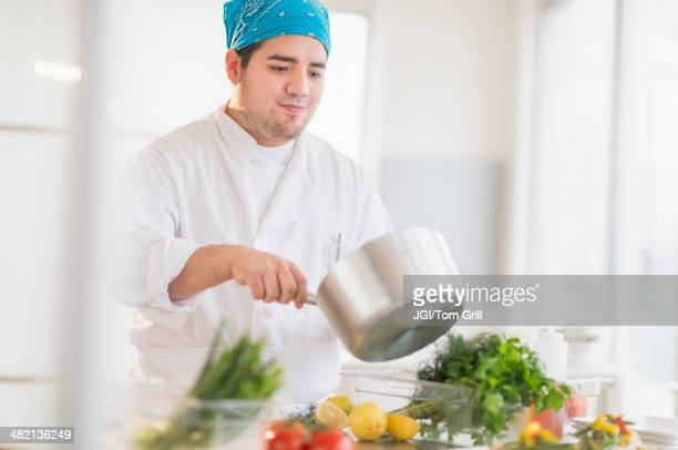 Mixed race chef cooking in restaurant