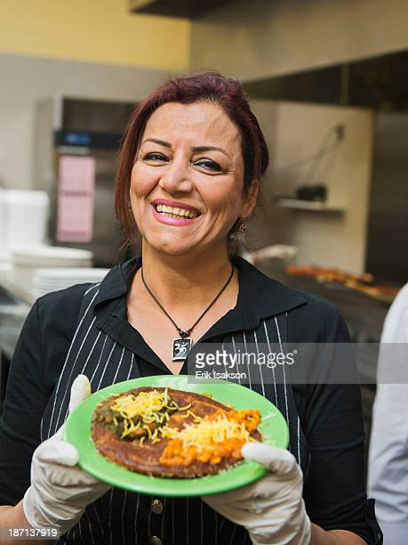 Mixed race chef holding plate of food in kitchen