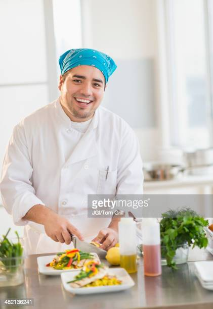 Mixed race chef plating food in restaurant