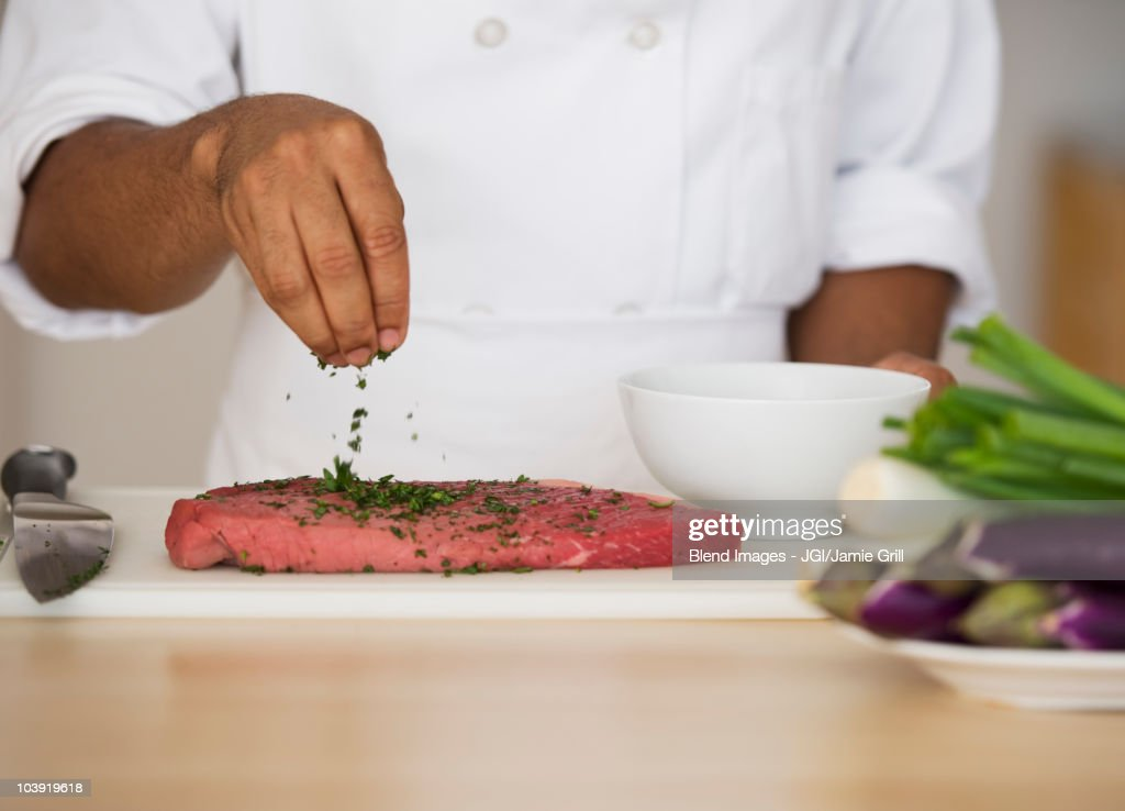 Mixed race chef seasoning steak