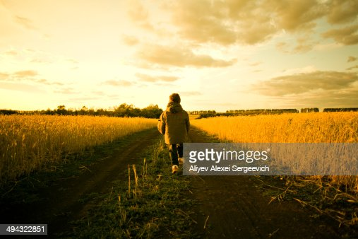 Mixed race child walking on path through rural field