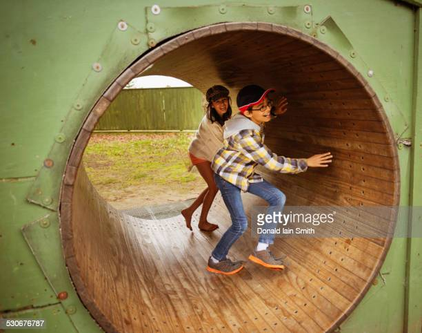 Mixed race children playing in wheel in playground