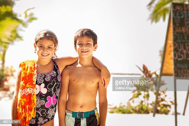 Mixed race children smiling on beach