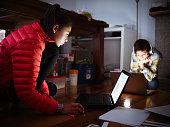 Mixed race children using laptops on floor