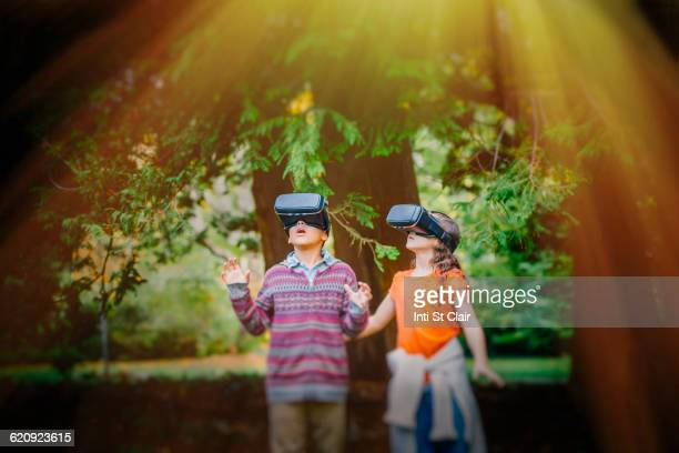 Mixed race children using virtual reality goggles outdoors