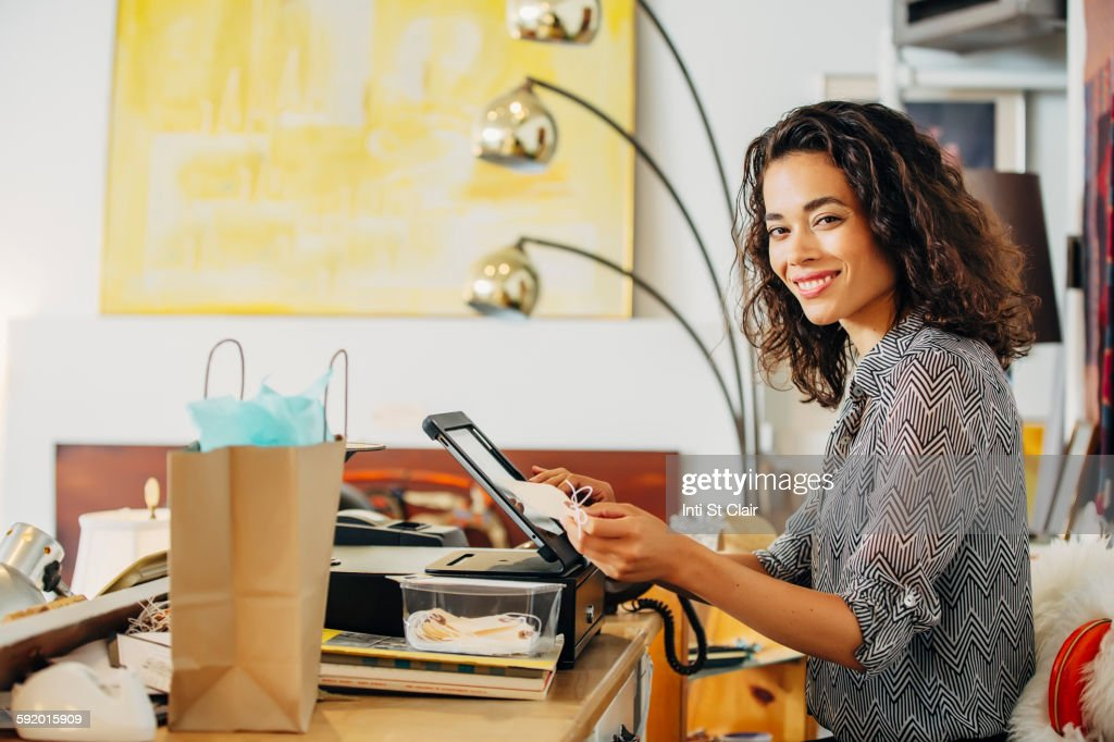Mixed race clerk using register in shop