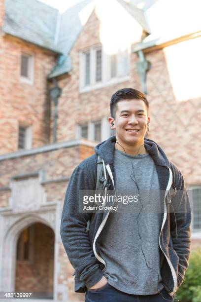 Mixed race college student listening to music on headphones