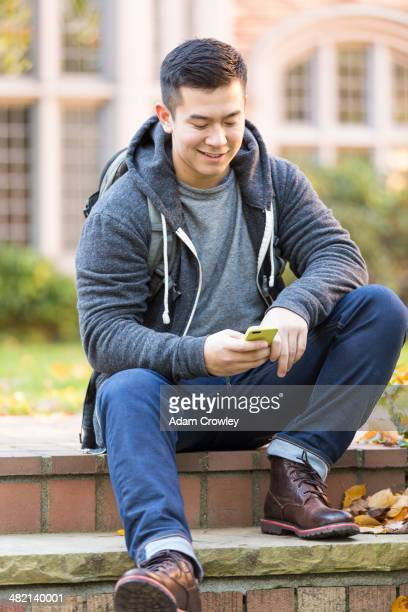Mixed race college student sitting on campus steps