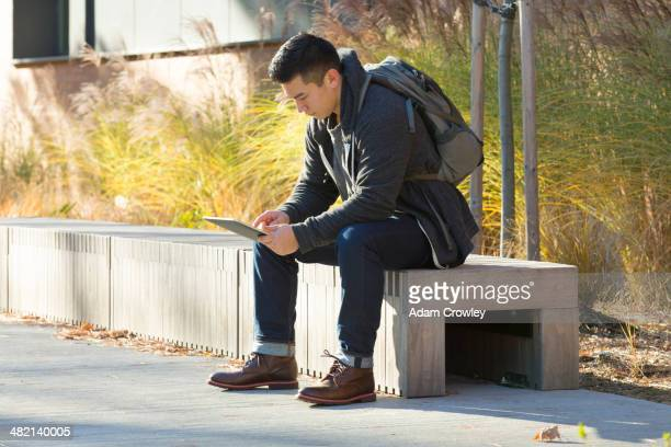 Mixed race college student using digital tablet on campus