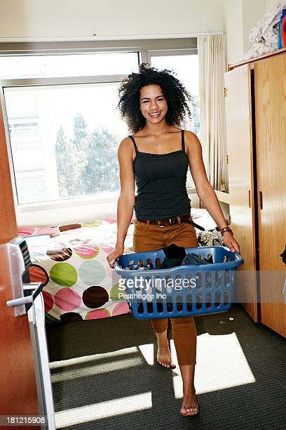 Mixed race college student with laundry in dorm