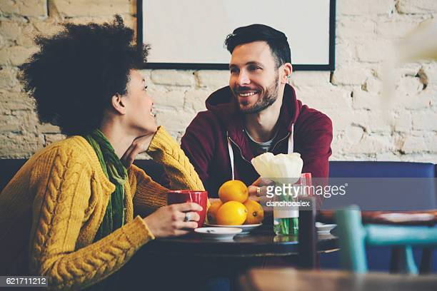 Mixed race couple at coffee house having coffee and chatting