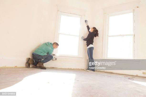 Mixed race couple cleaning wall new home