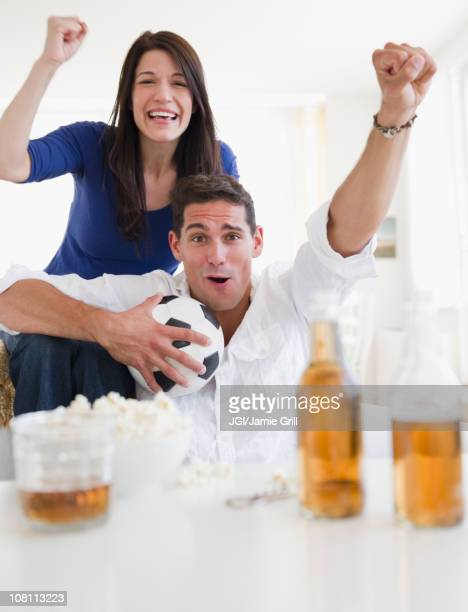 Mixed race couple drinking beer and cheering on soccer match
