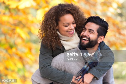 Mixed Race Couple Giving Each Other Piggy Backs