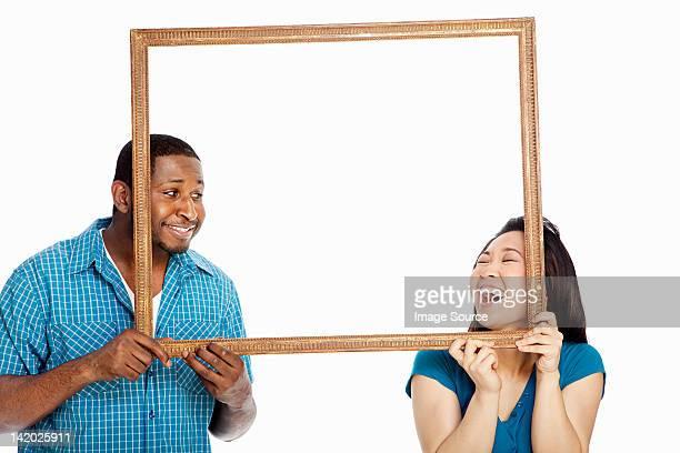異人種のカップルを持つフォトフレームと白い背景