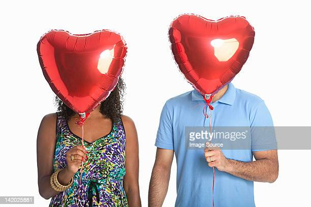 Mixed race couple holding red balloons against white background