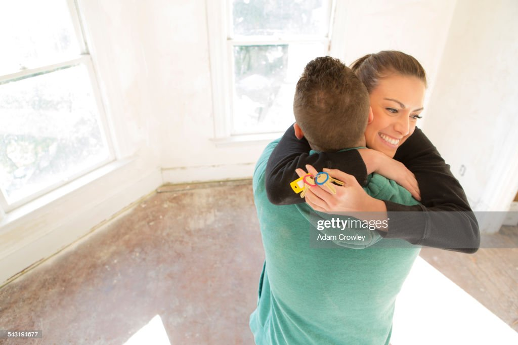 Mixed race couple hugging in new home