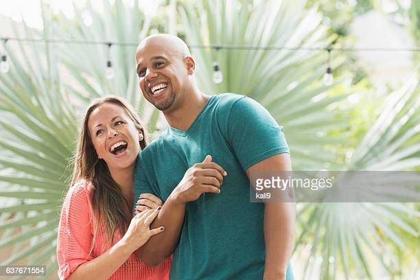 Mixed race couple laughing on tropical vacation