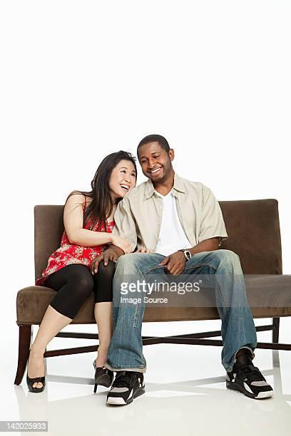 異人種のカップルの上にソファーと白背景
