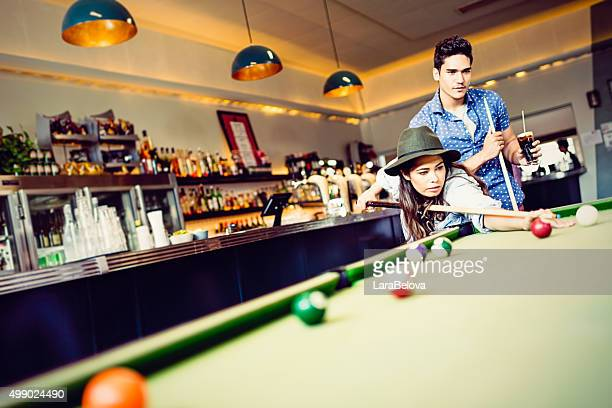 Mixed race couple playing pool game in pub