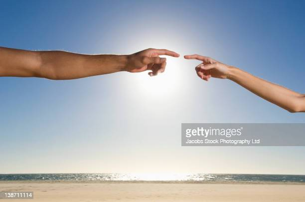 Mixed race couple pointing at each other
